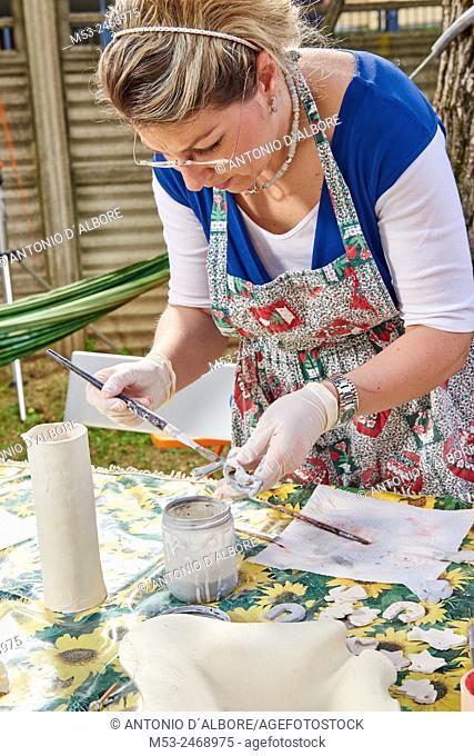 An amateur artist apply raku glaze on ceramic object