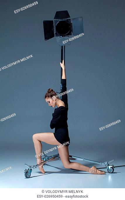 The beautiful ballerina posing on dack blue background in the studio with the flash
