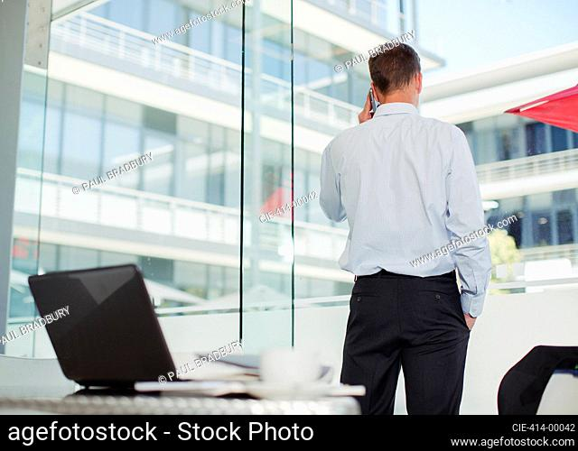 Businessman talking on cell phone at office window