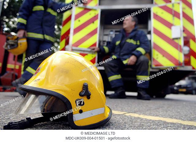 Two fire fighters from Hertfordshire Fire & Rescue Service, UK on a break. In the foreground is a new style yellow helmet with pull down sides and a protection...