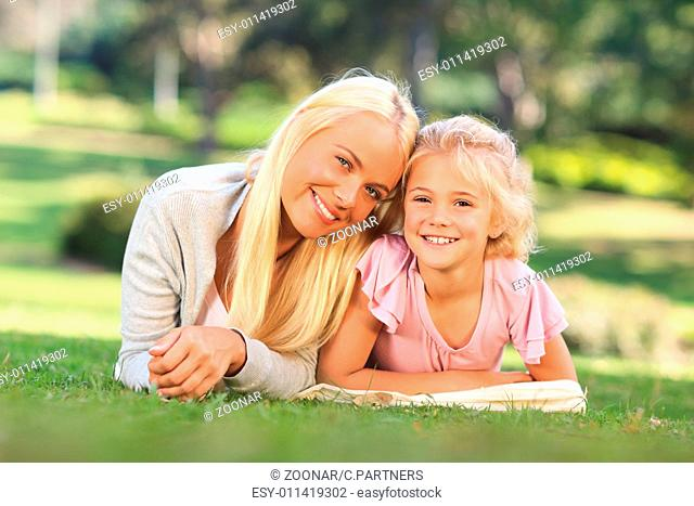 Mother with her daughter lying down in the park