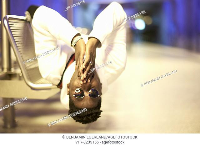 young man laying upside down on bench in underground train station, folded hands, in Munich, Germany