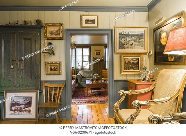 Old wooden chair and upholstered armchair in parlour room decorated with several paintings and doorway leading to living room inside an old circa 1805 Canadiana...