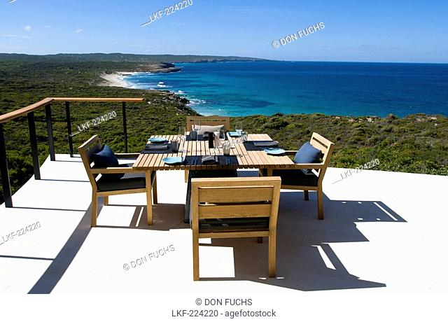 A table is laid at the terrace of the Southern Ocean Lodge in the sunlight, view at Hanson Bay, Kangaroo Island, South Australia, Australia