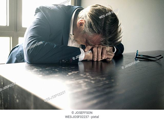 Mature businessman resting his head on the table