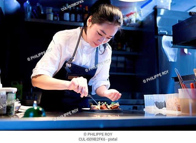 Chef in commercial kitchen seasoning food