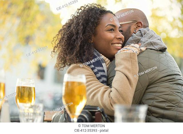 Smiling couple hugging and drinking beer at sidewalk cafe