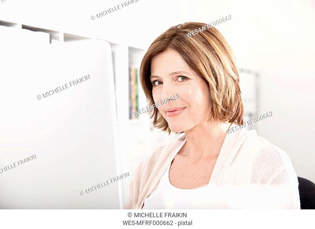 Portrait of smiling woman at her computer in the office