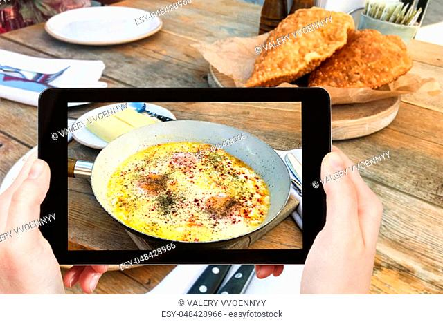 travel concept - visitor photographs of Fried Eggs with Sour Cream in Kabardian style in pan and hominy in local restaurant in North Caucasus region of Russia...