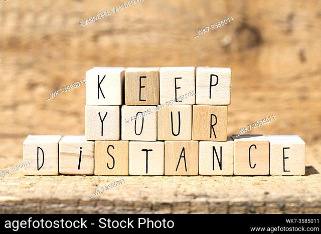 Wooden cubes with the words Keep Your Distance for Coronavirus and social distancing. wooden background closeup