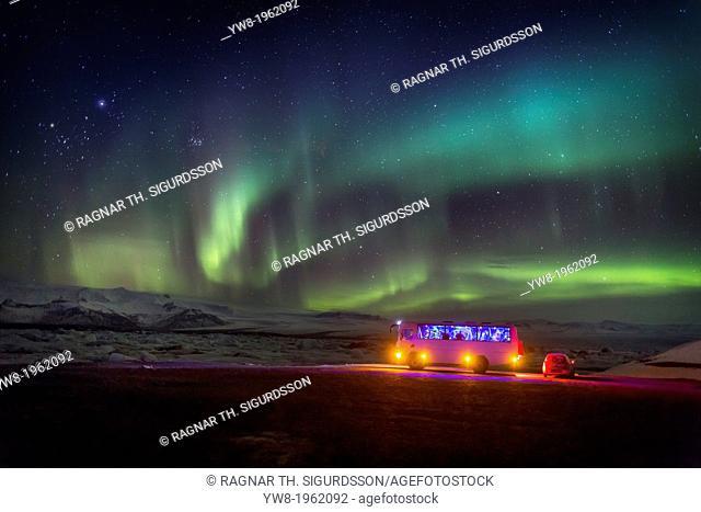 Aurora Borealis or Northern lights. Bus and car by the Jokulsarlon, Breidamerkurjokull, Vatnajokull Ice Cap, Iceland
