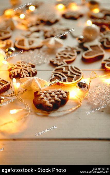 Christmas sweets composition. Gingerbread various shaped cookies with xmas decorations arranged on white wooden table with lights