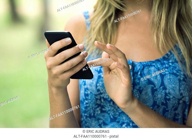Woman using smartphone, cropped