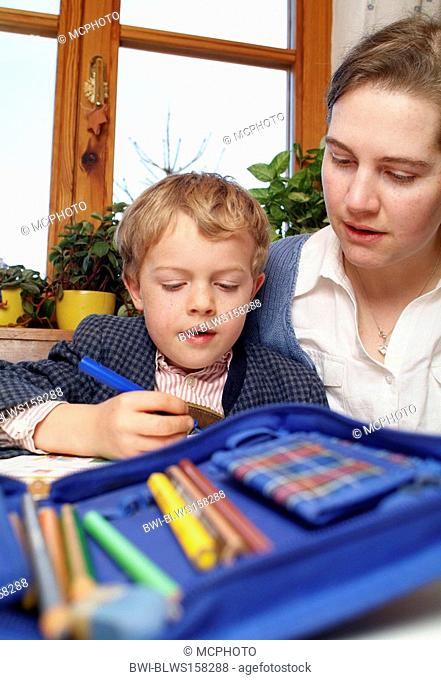 mother helps schoolboy with homework