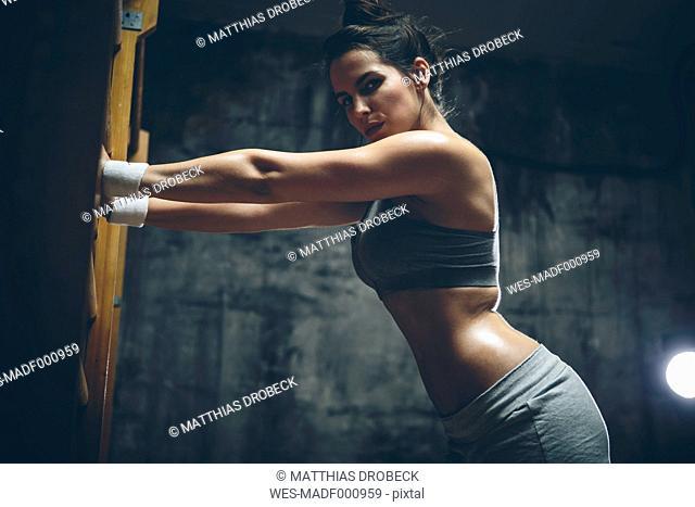 Female athlete exercising on wall bars