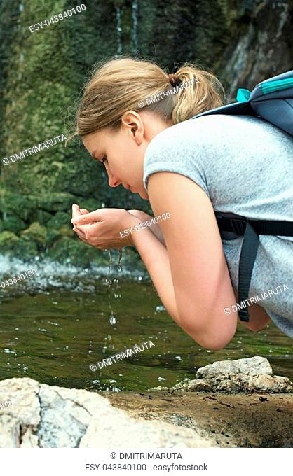 Woman with backpack drinking water from mountain spring