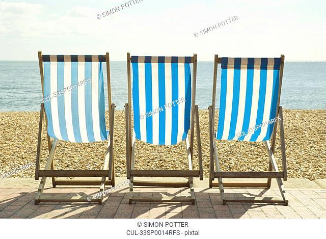 Striped lawn chairs on beach