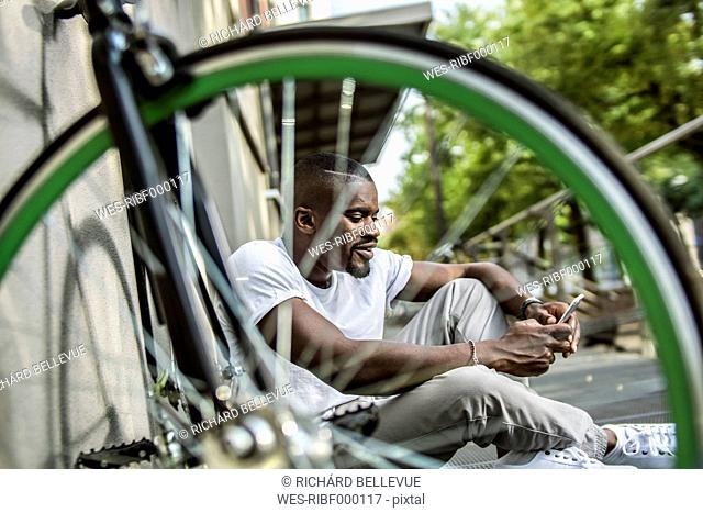 Portrait of young man sitting behind bicycle telephoning with smartphone
