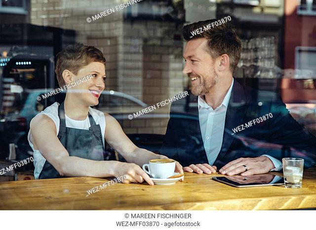 Waitress serving coffee to smiling customer in cafe