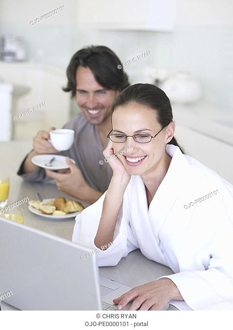 Woman in robe at laptop with man in background