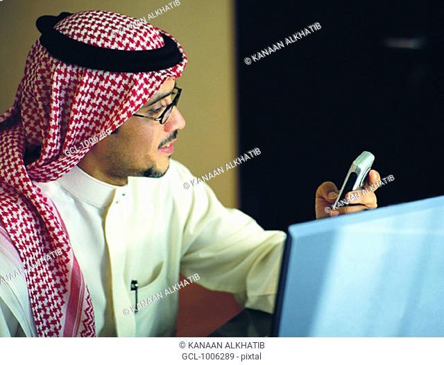 Saudi businessman using mobile phone and laptop