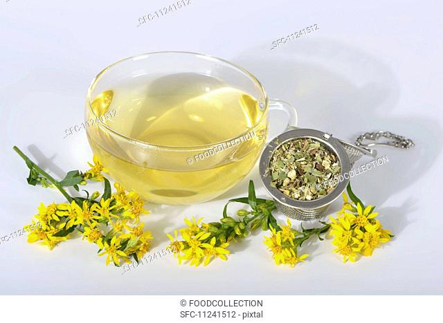 Goldenrod tea in a glass cup, dried tea leaves and fresh flowers