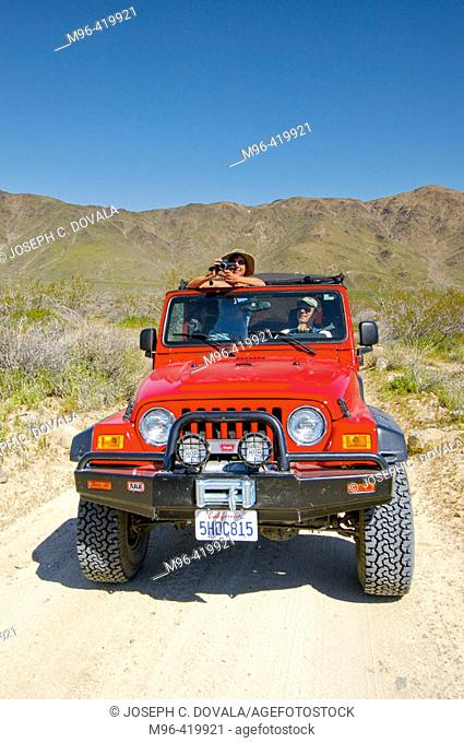 Caucasian man and woman in Jeep with video camera. Joshua Tree Park. California. USA