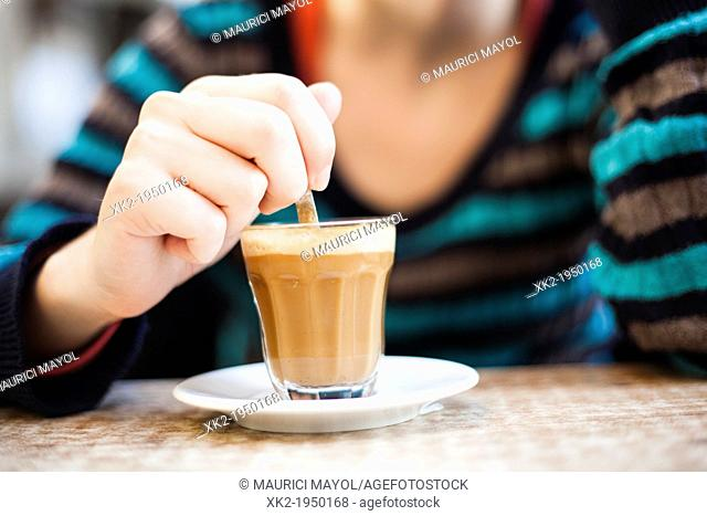 Detail of woman's hand mixing latte coffee with a spoon