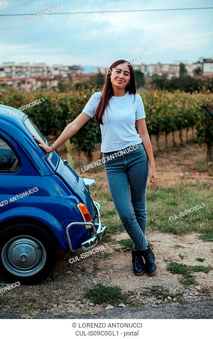 Portrait of woman leaning against car in countryside, Florence, Toscana, Italy