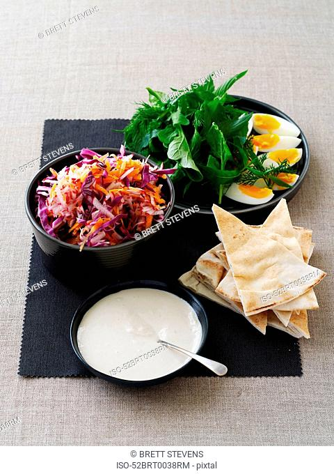Bowls of eggs, salad and dipping sauce
