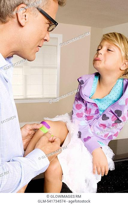 Man applying bandage on his daughter's knee