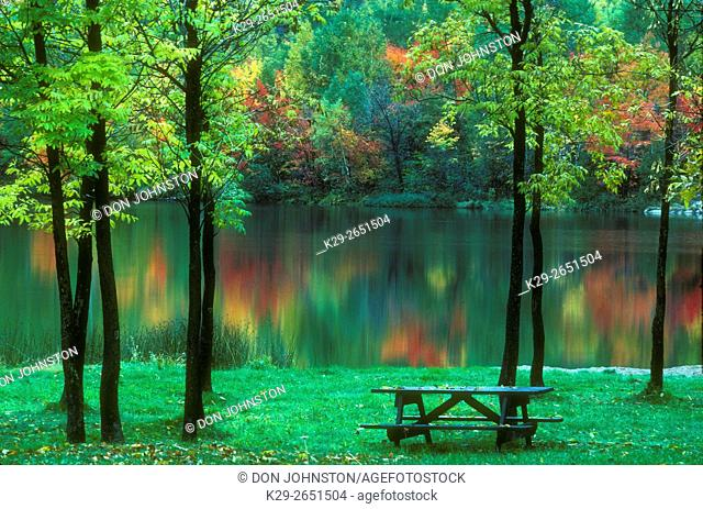 Autumn colour reflected in Simon Lake, with picnic grounds, Naughton, Ontario, Canada