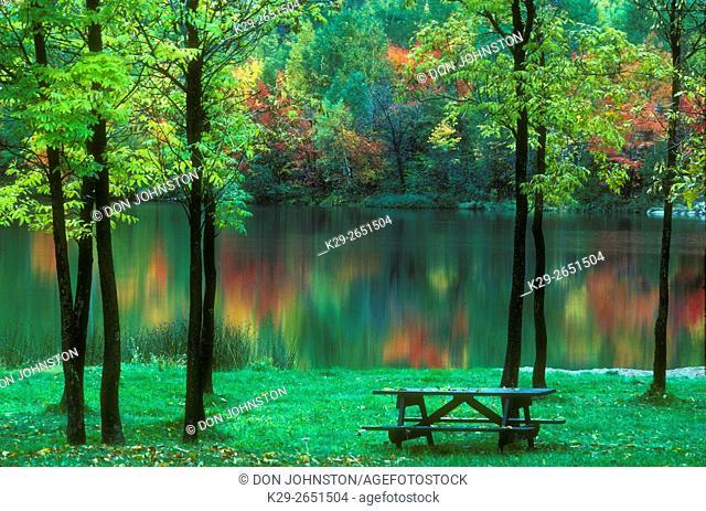 Autumn colour reflected in Simon Lake, with picnic grounds, Naughton, Ontario, Canada