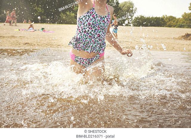 Caucasian girl splashing in waves on beach