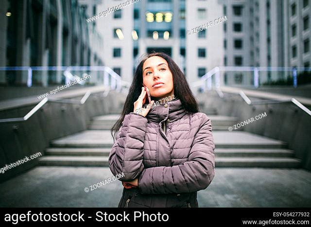 young girl talking on mobile phone in courtyard business center. girl with long dark hair dressed in winter jacket in cold weather speaks on phone on background...
