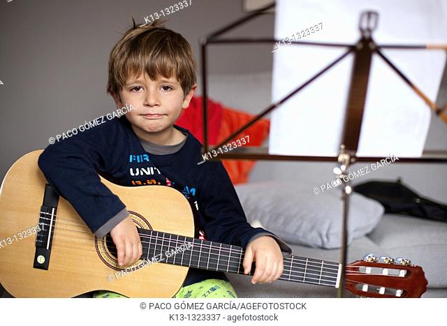 Child rehearsing with guitar