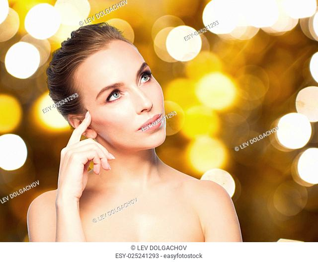 beauty, people and holidays concept - beautiful young woman touching her face over lights background