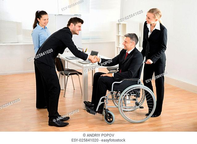 Mature Businessman In Wheelchair Shaking Hands With Colleague In The Office