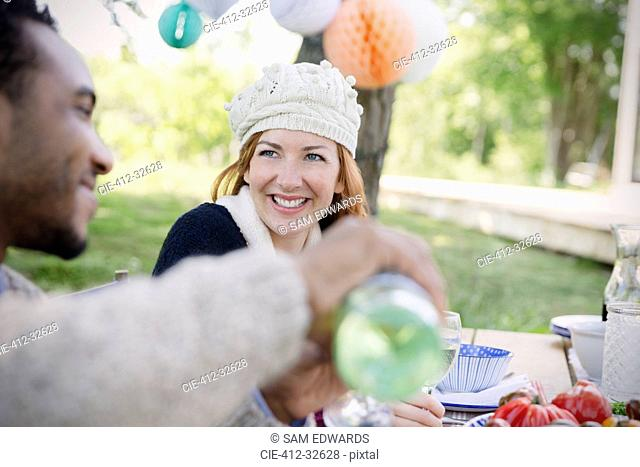 Smiling couple pouring wine at patio lunch table