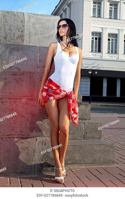 leggy beautiful lady standing on sidewalk of city