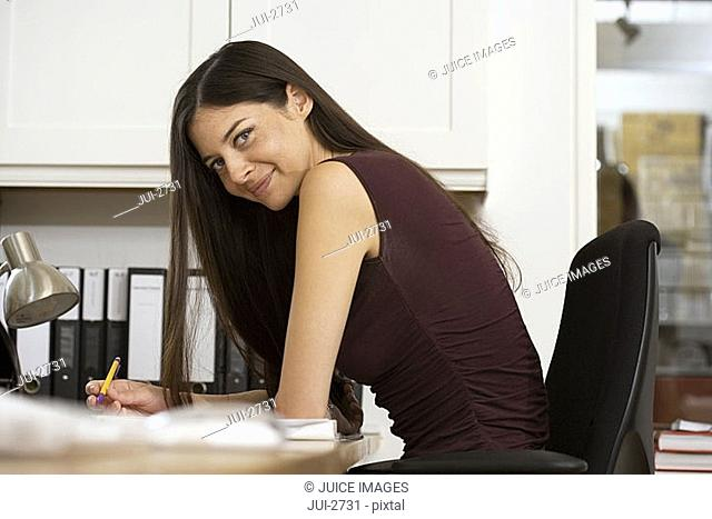 Businesswoman in sleeveless top working at desk in office, holding pen, smiling, side view, portrait