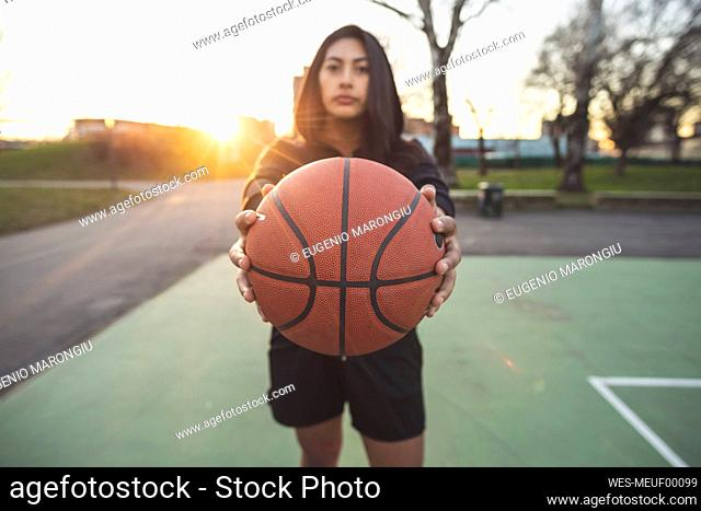 Young sportive woman posing holding basketball on court at sunset