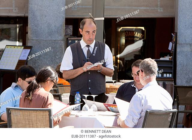 Waiter taking orders from diners at a restaurant in the Plaza Mayor