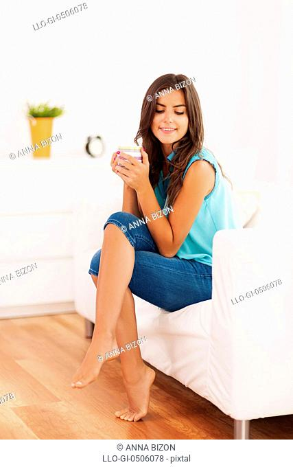 Pretty woman relaxing with cup of coffee at home, Debica, Poland