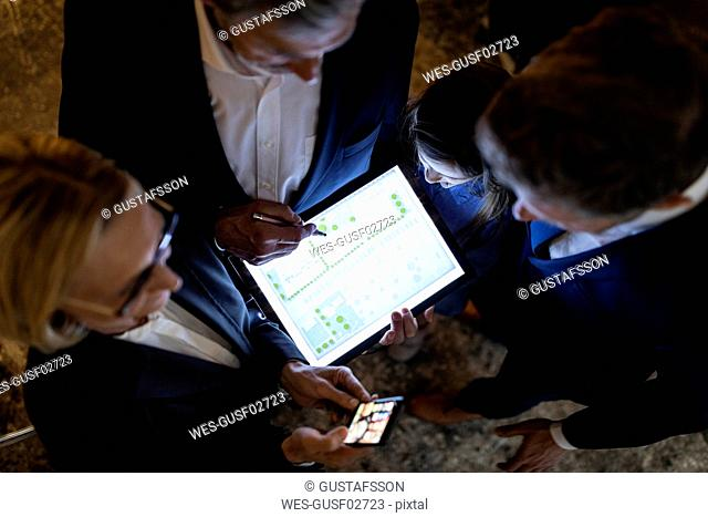 Top view of business people and girl looking at shining construction plan on tablet in office