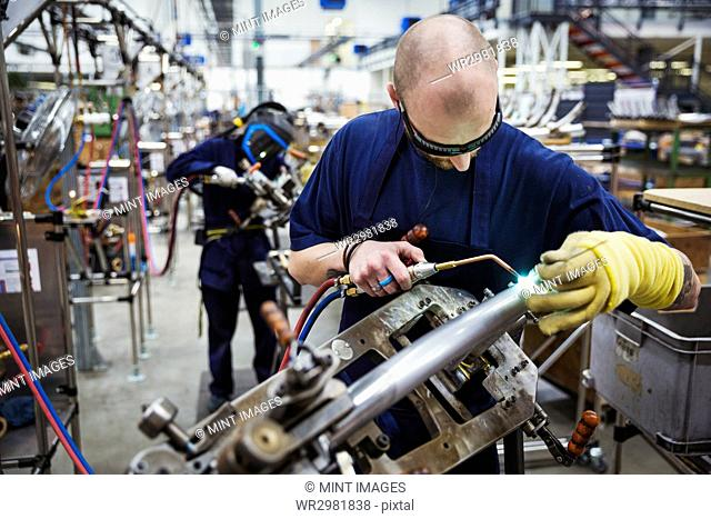 Male skilled factory worker wearing protective glasses, using a welding tool, working on a bicycle in a factory