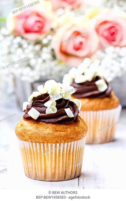Chocolate cupcakes for wedding reception. Bouquet of pink roses in tha background