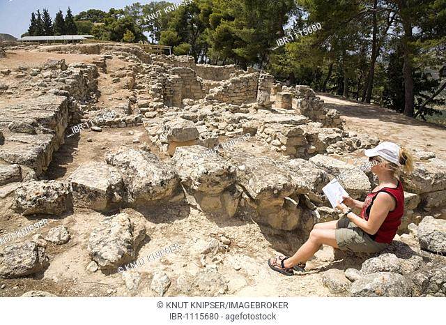 A tourist sitting amid the excavation site of the Minoan palaces of Festos, island of Crete, Greece, Europe