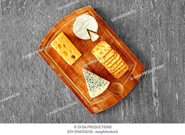 different cheeses and crackers on wooden board