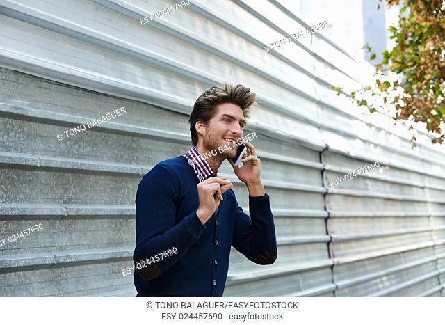 Young businessman talking smartphone phone on the street metal fence